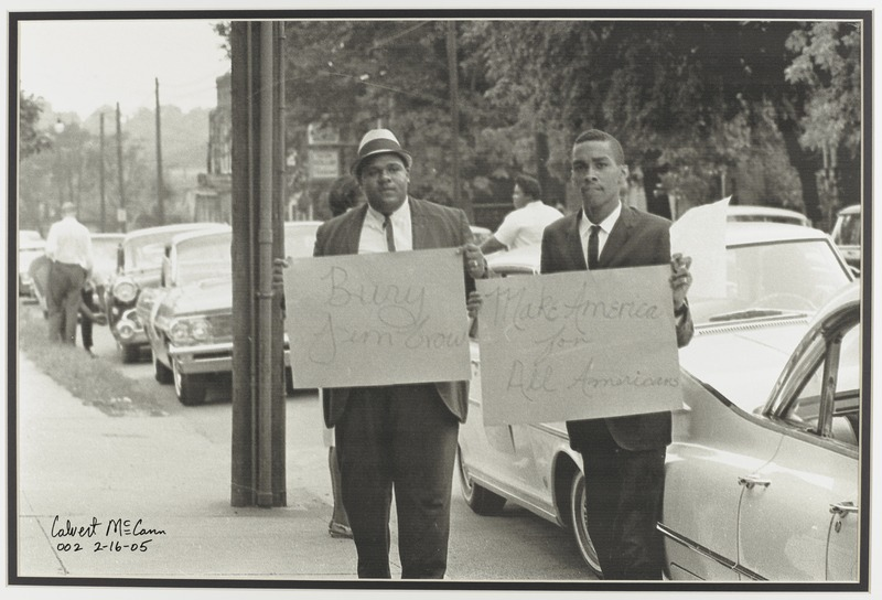 """Demonstrators hold signs reading """"Bury Jim Crow"""" and """"Make America for all Americans"""""""